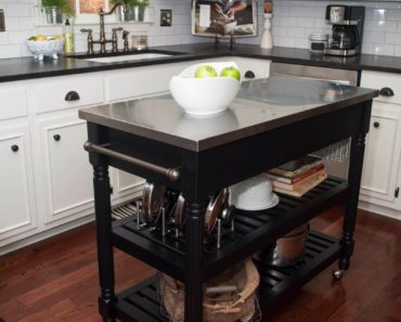 white kitchen with dark portable kitchen island on wheels