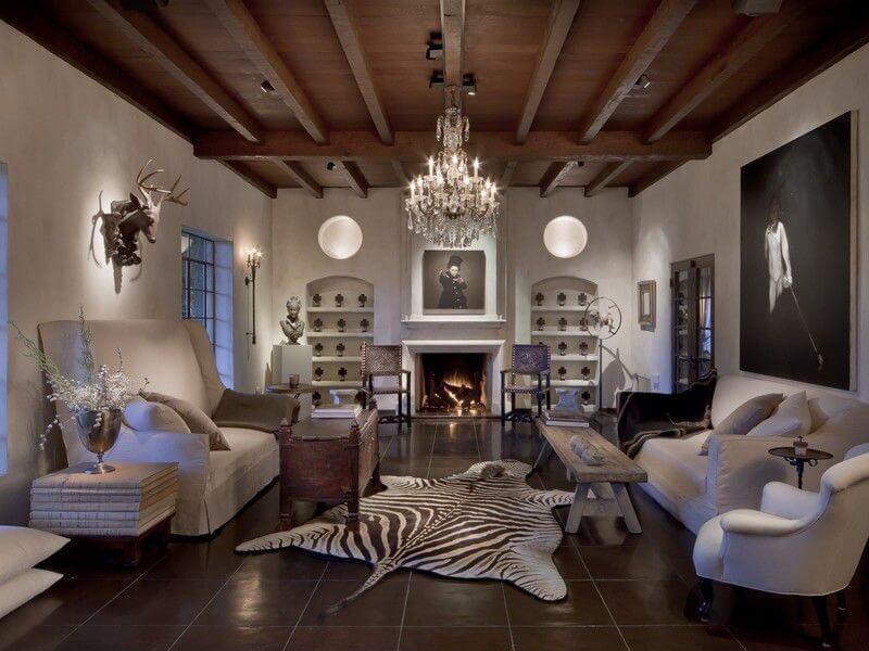 Grand salon avec sol en carrelage marron foncé sur lequel une grande peau de zèbre est placée comme décor du sol central entre un canapé à dossier haut, un banc en bois, un canapé à dossier régulier et une chaise de lecture.