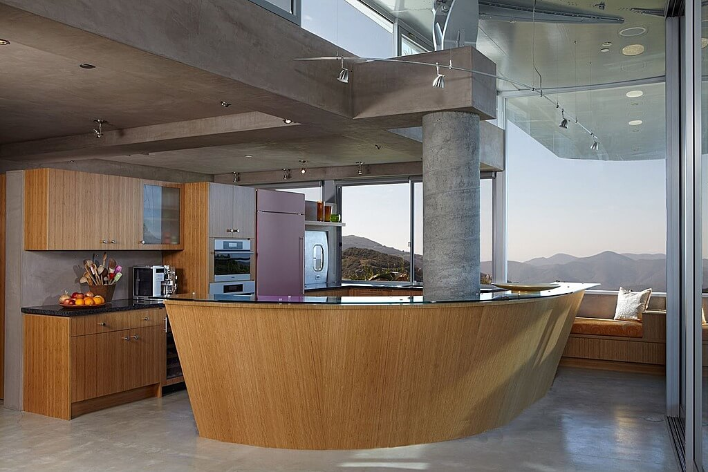 Ultra modern kitchen featuring slanted, natural wood island with glass countertop connected to large central concrete pillar.