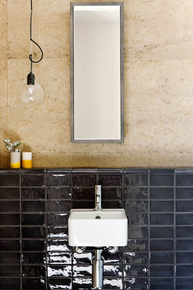 Floating sink design mounts against dark tile wall, beneath vertical oriented mirror on rammed-earth-based wall.