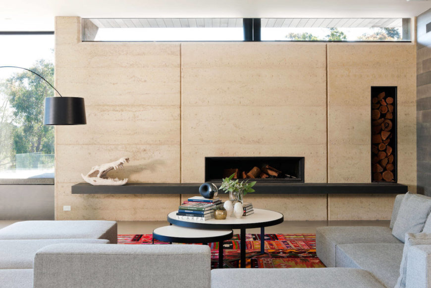 Head-on view of slim fireplace built into the wall in the living rom, with lengthy dark wood mantle and in-wall firewood storage.