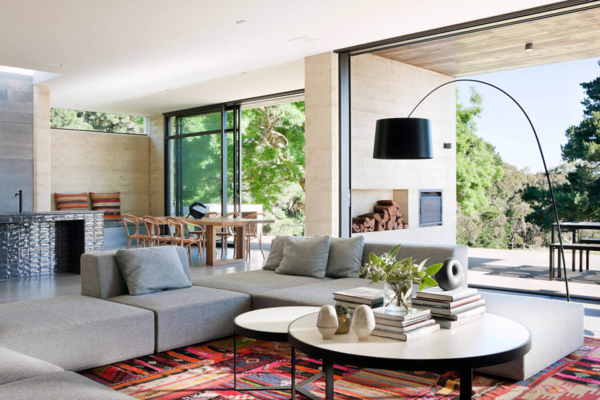 Central open living room space pictured here, with large grey U-shaped sectional centered around tiered circular coffee tables, over brightly colored area rug. Floor to ceiling glass affords view to outdoor space, while dining room and kitchen are pictured in background.