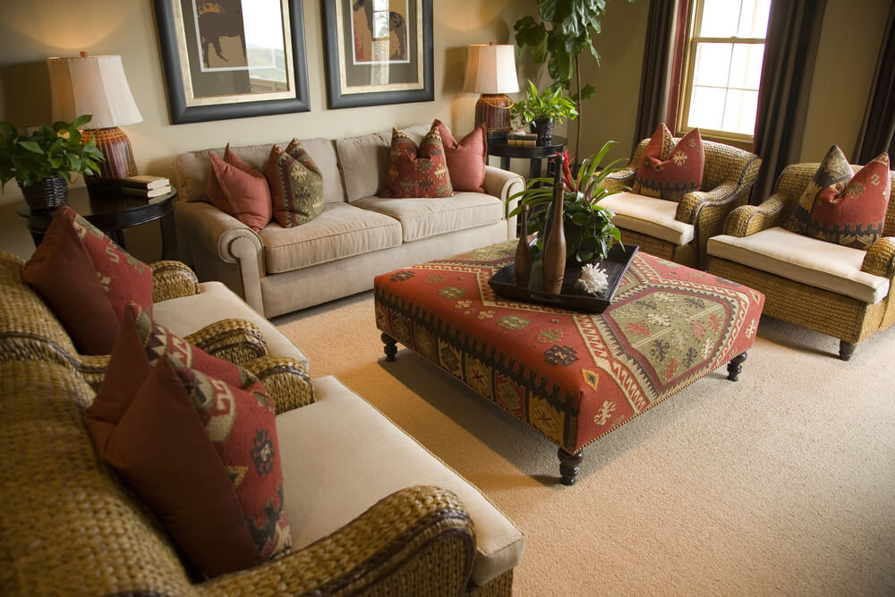 living room in earth tones and splashes of red with an ottoman