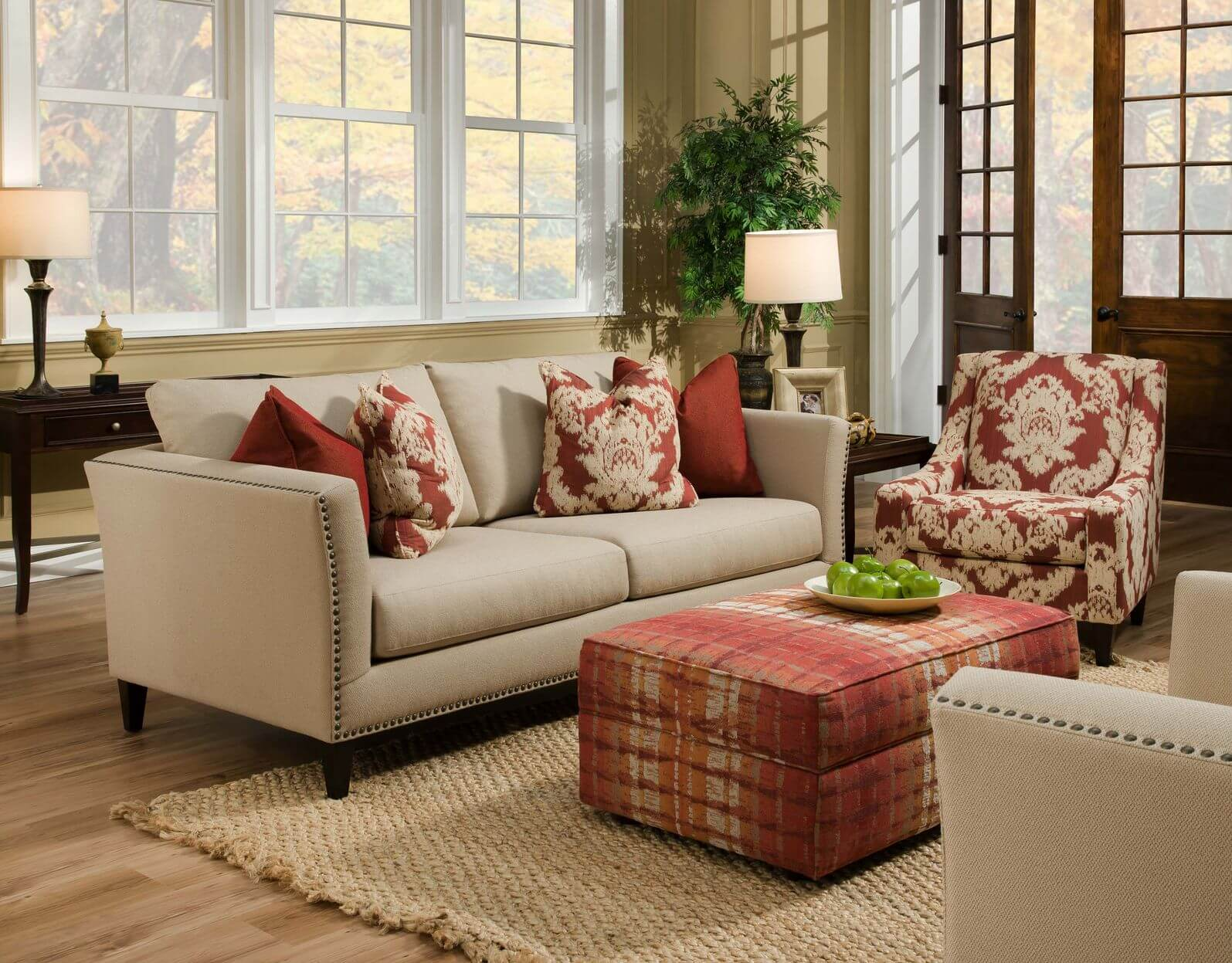 Beige twin couches face each other over natural hardwood flooring and tan rug in this living room featuring red patterned fabric rectangle ottoman.