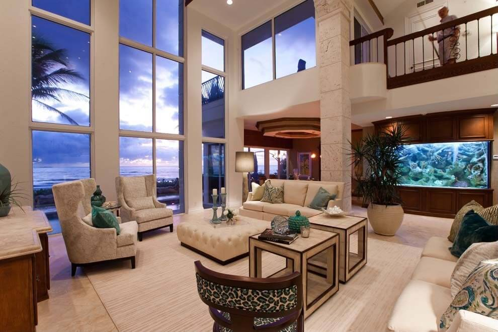 Two Story Living Room Featuring Floor To Ceiling Views Of The Ocean Features Beige Toned Furniture