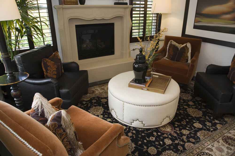 Cozy living room with commanding stone fireplace features alternating orange and black armchairs orbiting nail head trimmed white leather ottoman with portable wood surface tray.