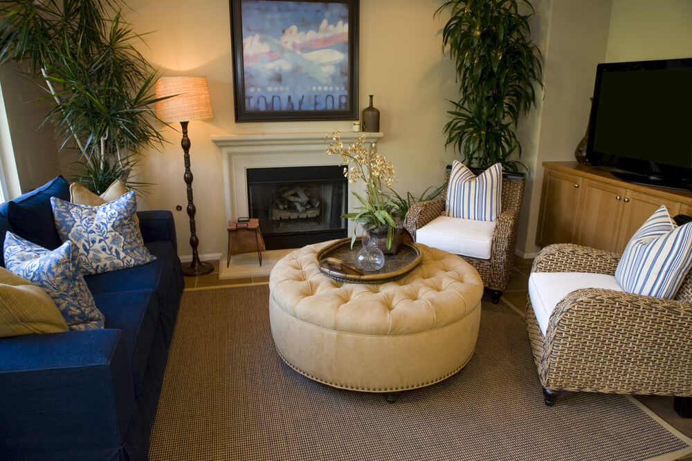 Cozy living room centers round button tufted and nail head trimmed ottoman between twin wicker armchairs and navy blue sofa.