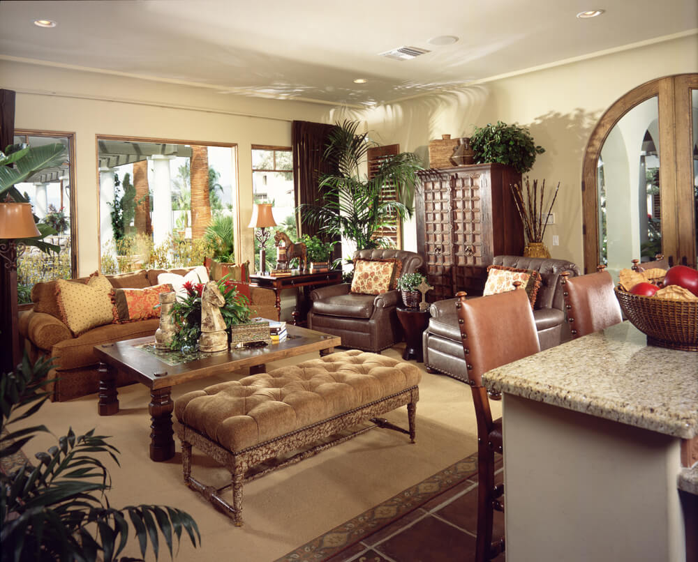 Luxurious living room awash in multiple exotic textures, featuring marble topped bar table, leather easy chairs, overstuffed orange sofa and large tufted bench ottoman next to hardwood coffee table.