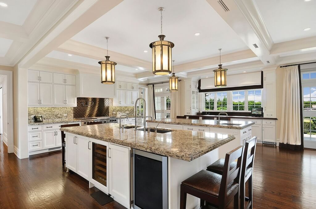Huge white kitchen with dark wood flooring. The wall of windows provides plenty of natural light. This kitchen includes and exceptional amount of working surface area as a result of two massive kitchen islands (each with a sink).