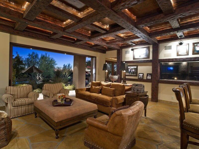 Plethora of dark wood exposed beams define this living room, with open wall to garden next to furniture set surround large cushion-topped, carved wood ottoman.