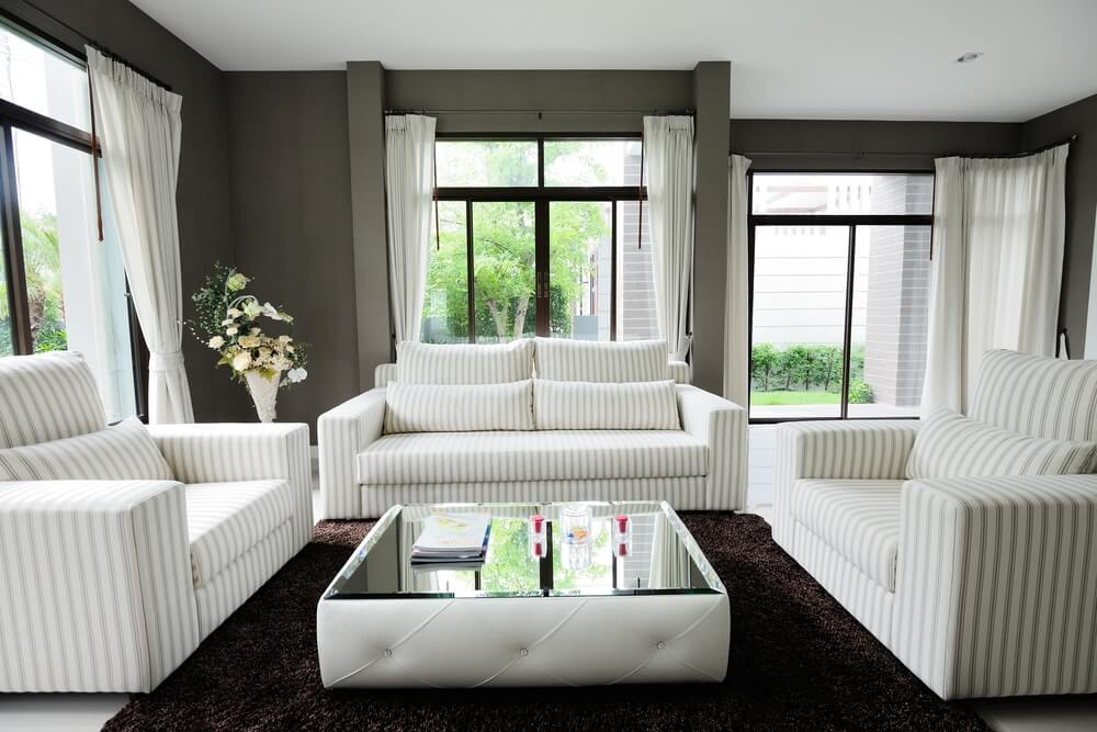 Unique low profile square white tufted ottoman centers this living room with full mirrored table top surface over dark rug on white marble flooring.
