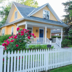 Quaint yellow house with white picket fence