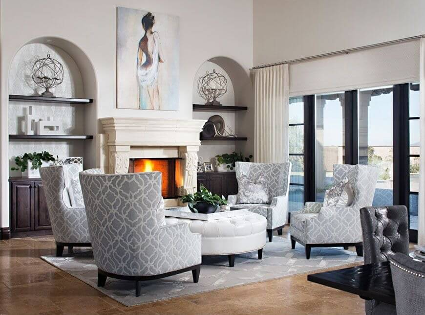 High ceiling living room featuring dark wood shelving in arched wall coves flanking white fireplace, with four armchairs seated around large white circular tufted leather ottoman with removable table top.