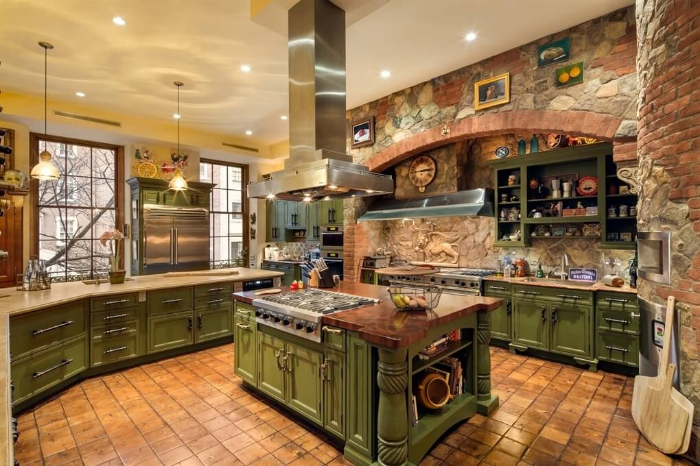 Intricate country kitchen with brick and stone work throughout. Cabinetry is a textured green. Kitchen layout is sprawling with several work areas.