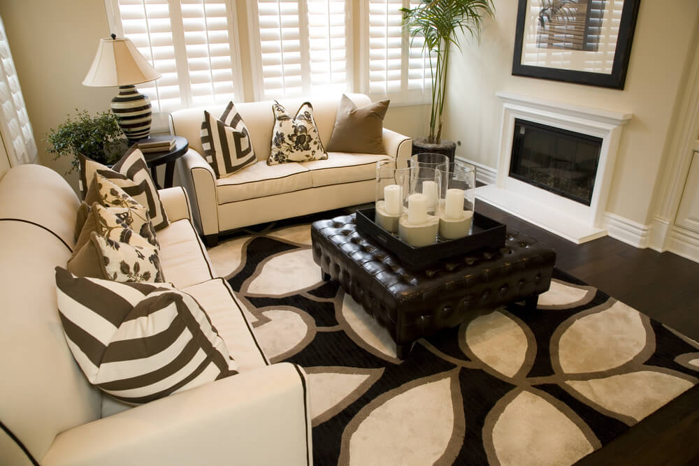High contrast themed living room features white sofas with black trim, patterned rug over dark hardwood flooring, white fireplace, and large square dark tufted leather ottoman at center.