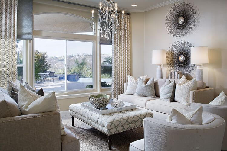 Light beige tones dominate this living room, featuring matching couch and chair set around rectangular patterned fabric ottoman with white removable table surface.