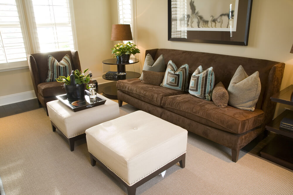 Compact living room with dark mocha chair and armless sofa, contrasting with white single-button tufted twin ottomans.