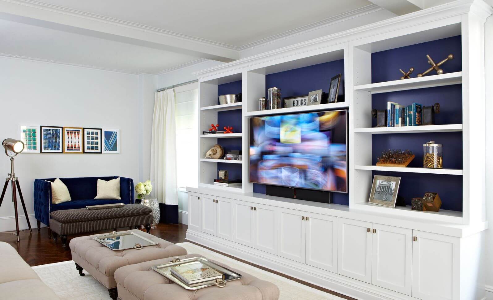 Blue and white living room - Bright White Walls And Cabinetry Contrast With Dark Natural Wood Flooring In This Living Room Featuring
