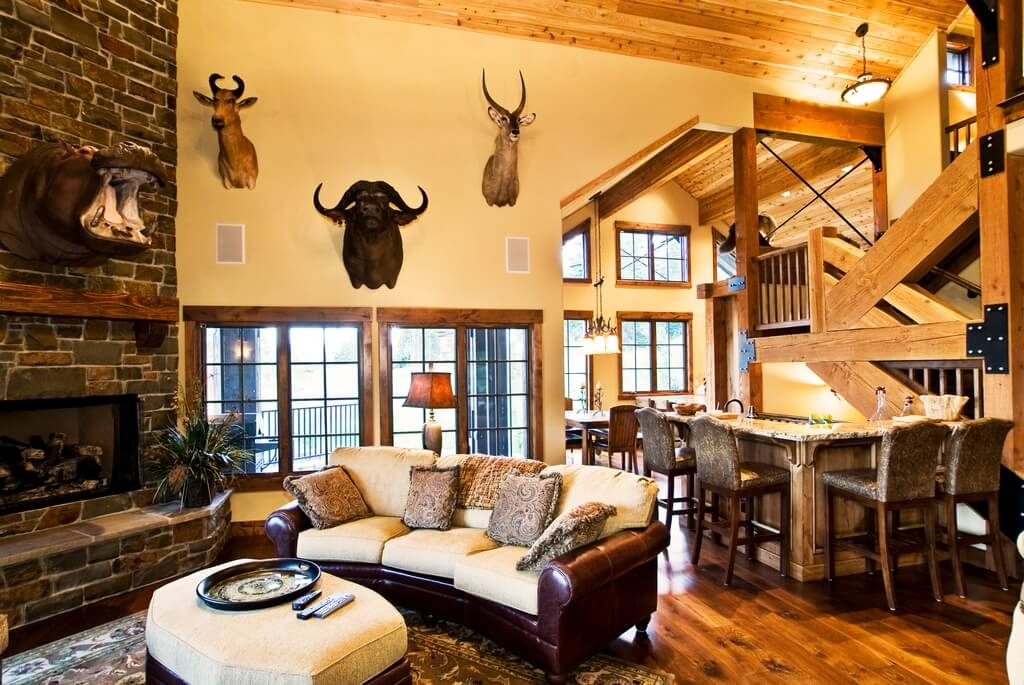 Exposed natural wood beams and mounted trophy animals give this open living space a rustic feel, with rolled arm leather and linen sofa matching cushion-topped ottoman with removable tray surface.