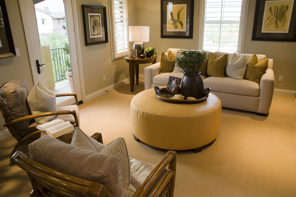 Warm yellow round cushioned ottoman stands at center of this cozy living room, awash in natural earth tones.