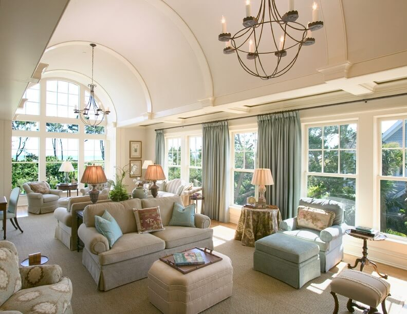 Large, arched ceiling living room with extensive windows for natural lighting features multiple ottomans, including carved corner rectangular model at center, with trey table on cushion top.