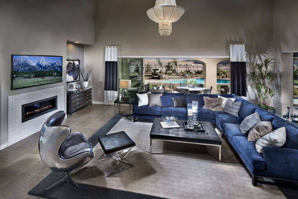 Expansive, open living room on grey tile flooring features lengthy blue fabric sectional sofa and chrome-backed swivel arm chair, with large metal frame black tufted leather square ottoman table at center.