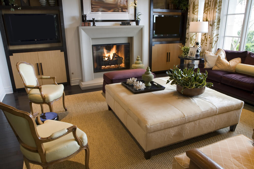 Tightly matched living room features beige, brown, and purple accents throughout, with smaller purple rectangular ottoman butted against large square beige ottoman with portable tray table surface and house plant on top.