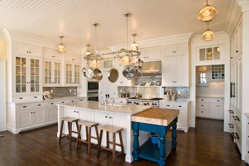 Luxurious white kitchen with wood floor with a splash of color provided by a bright blue portable butcher block