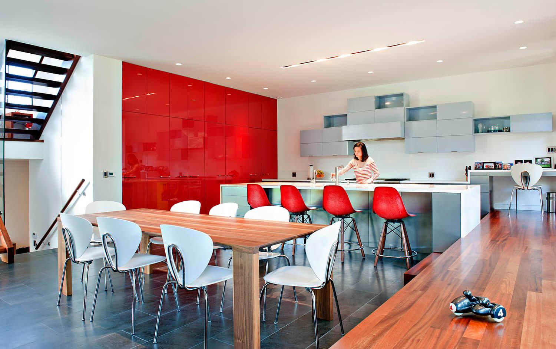 La cuisine est inondée d'une multitude de textures et de tons, avec un salon surdimensionné en bois naturel, des placards rouges plus brillants sur le mur de gauche et un assortiment de placards minimalistes gris montés au-dessus du comptoir.  Les sièges de bar sur une grande île blanche et un bureau dans un coin ajoutent à la polyvalence.