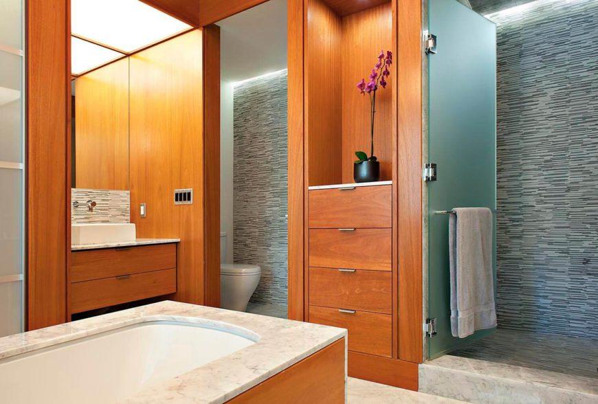 """Les salles de bains sont décorées de marbres et de bois franc naturel clair, avec une baignoire """"îlot"""" centrale et une douche à porte vitrée.  Un lavabo au-dessus du comptoir apparaît à gauche."""