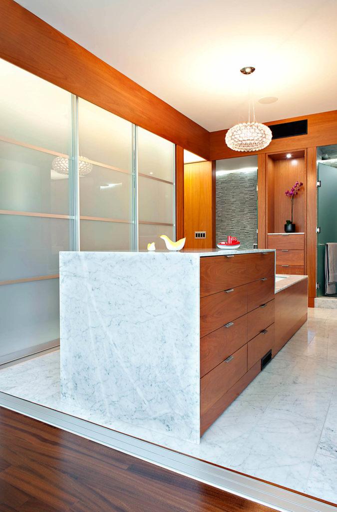 Longue vue de la salle de bain, soulignant le sol en marbre et le pourtour de la baignoire, avec rangement pour tiroir en bois intégré.  Caractéristiques du mur d'intimité en verre fumé à gauche.