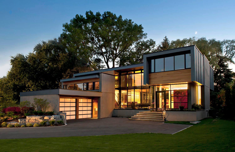 Enfin, l'extérieur de la maison brille la nuit.  Les parois en verre pleine hauteur exposent une lumière chaude et douce et des éléments de structure élégants et minimaux.