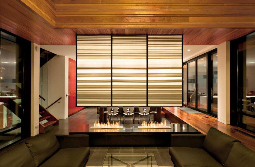 Voici un aperçu du salon ouvert la nuit, avec une cheminée à gaz ouverte sous un mur de séparation suspendu éclairé de l'intérieur.