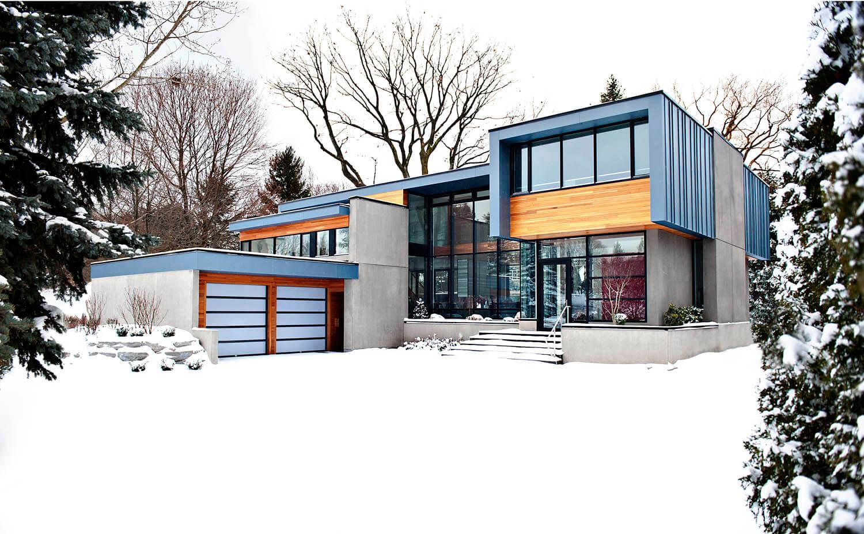 Contrairement à la première image, nous voyons la maison ici dans un décor hivernal, mettant en valeur les tonalités audacieuses et lumineuses de l'extérieur, associant zinc bleu, cèdre espagnol et béton pour une présence résolument moderne.
