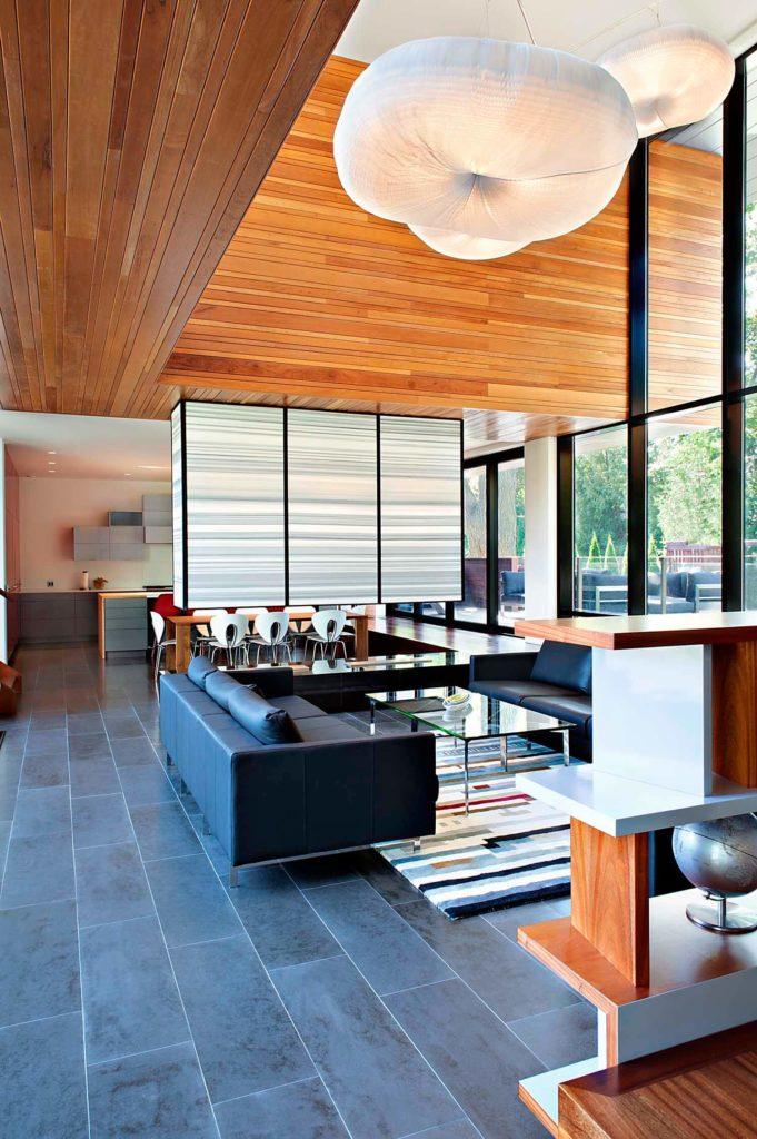 """Voici le salon central, visible à la lumière du jour.  Un sol gris ardoise avec un tapis de couleur à motifs assis entre deux canapés en cuir ancrent l'espace ouvert sous des lustres uniques """"en nuage""""."""