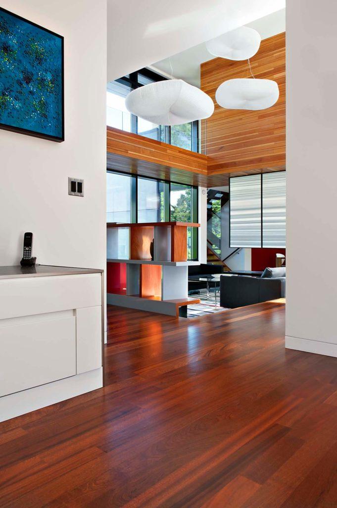 Le riche parquet en merisier et les murs blancs offrent un contraste, avec une passerelle supérieure en bois naturel plus léger et des panneaux de plafond gardant un aspect naturel.  L'étagère d'art définit le bord de la salle de séjour submergée.