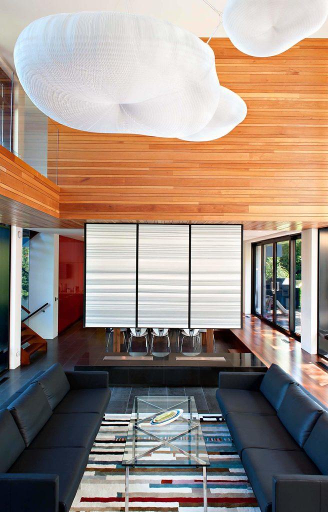 Vue directe sur le coin salon: des canapés bas en cuir taillés donnent sur une table basse en verre et en métal poli, avec un mur de séparation blanc suspendu séparant l'espace repas.