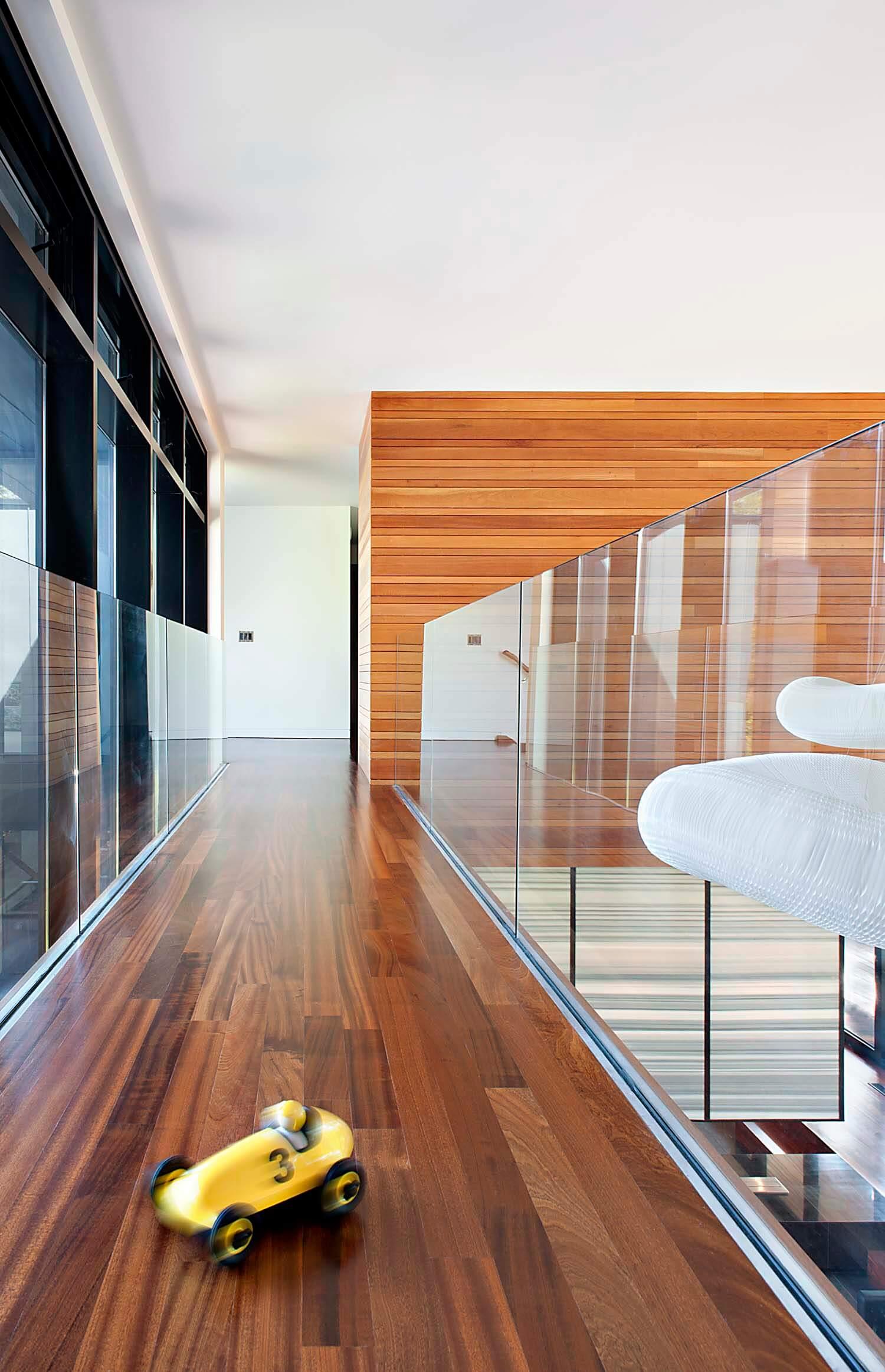 Passerelle supérieure gardée par des balustrades en verre, avec un riche parquet en bois franc foncé au deuxième étage.