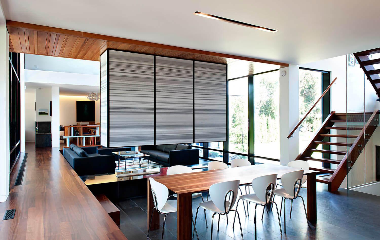 Ici, nous avons le côté salle à manger de l'intérieur central ouvert, avec une table en bois naturel pouvant accueillir huit personnes, un escalier en bois foncé à droite et un couloir surélevé à gauche.