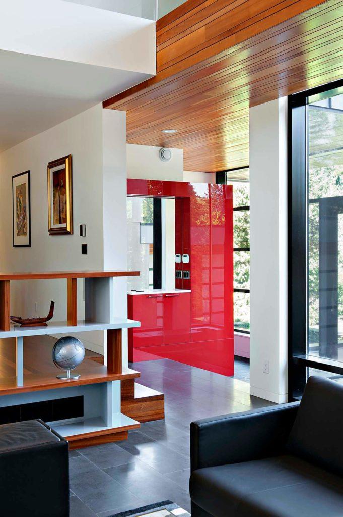 La vue depuis le salon vers l'entrée principale met en valeur le bois naturel luxuriant utilisé dans l'ensemble et le centre des armoires rouges et brillants.