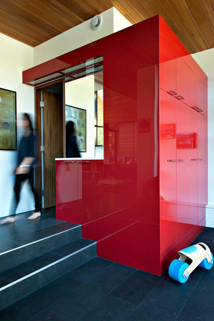 Cette touche unique ajoute une touche de couleur artificielle à la maison, avec des surfaces brillantes dissimulant une abondance d'espace de stockage et accueillant les invités qui arrivent.