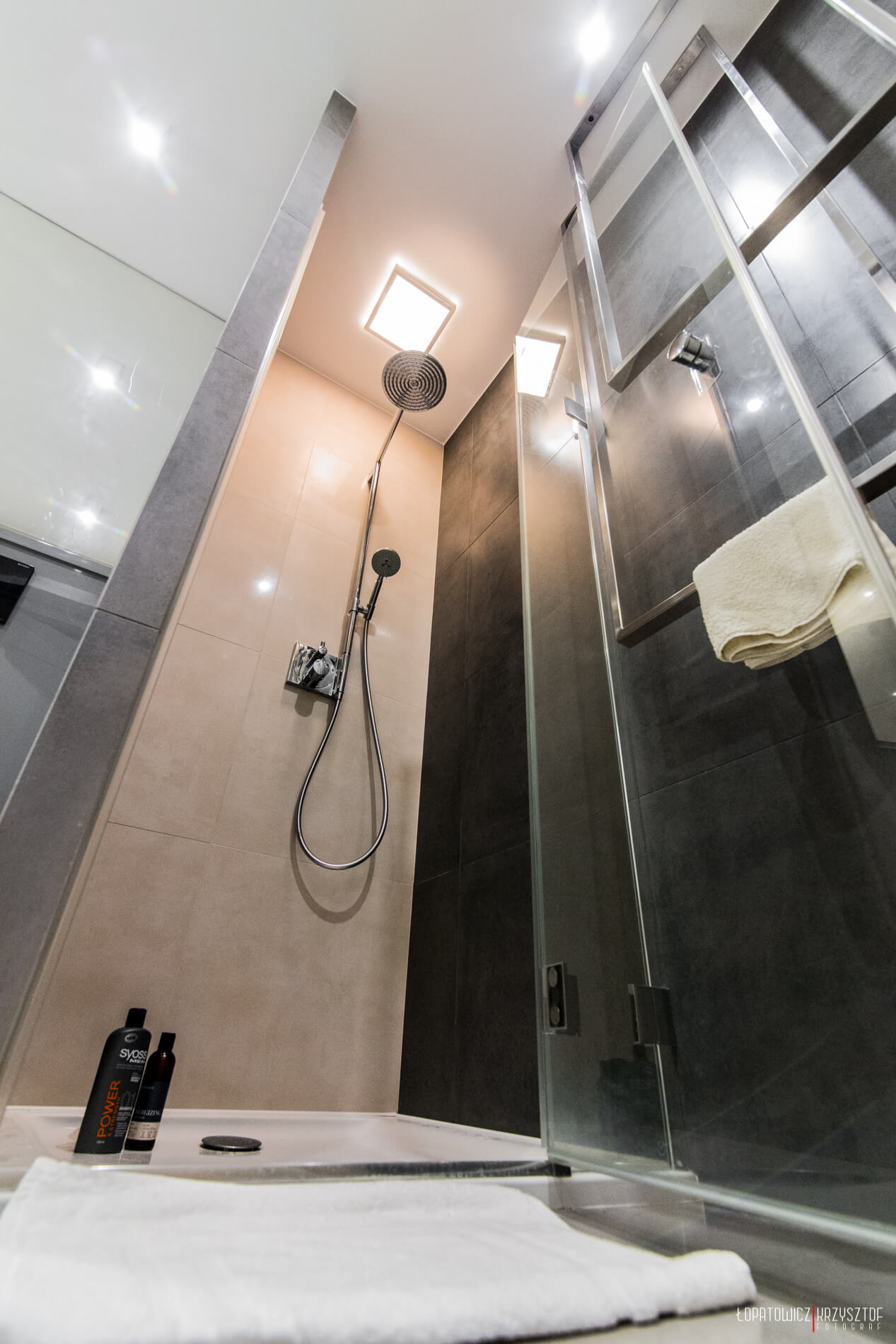 Low view of shower stall, showcasing floor to ceiling marble trim and glass door, plus in-shower ceiling light.