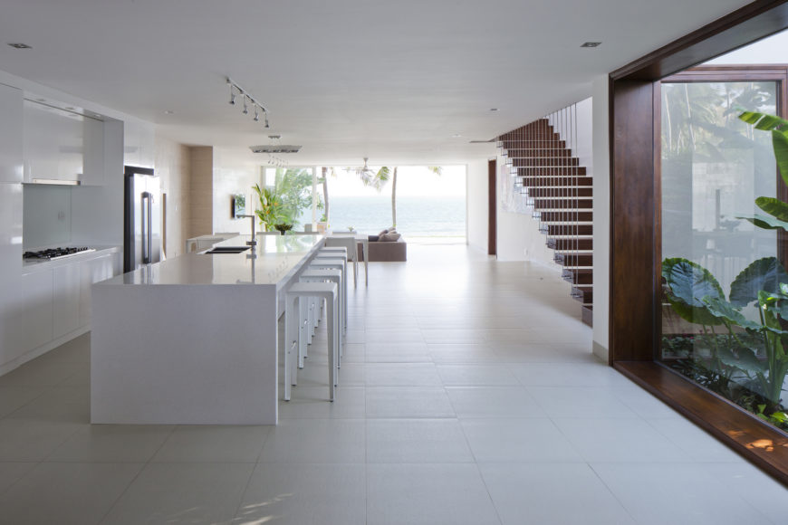 Central open interior space holds this kitchen area, replete with large white marble island with extensive dining space over white tile flooring. Wood framed window at right affords view of garden pond.