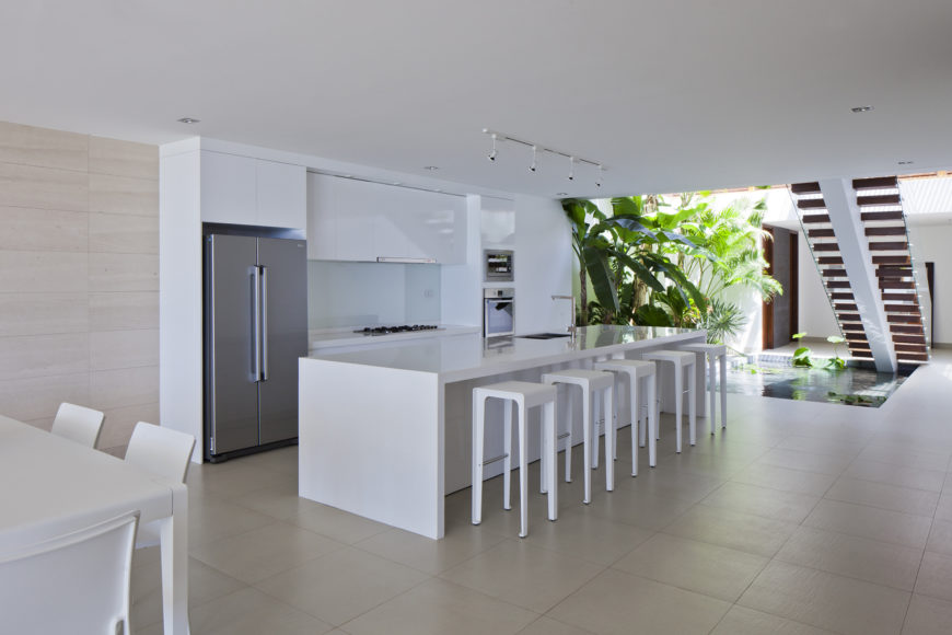 Here's another of the kitchen space examples, this one incorporating the pond space beneath central wood step staircase.