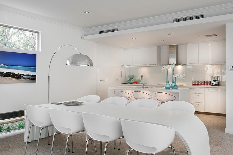 Close view of the dining table reveals an intriguing arched creation, a single white slab forming the legs and surface. Kitchen stands behind under drop-ceiling in all-white as well.