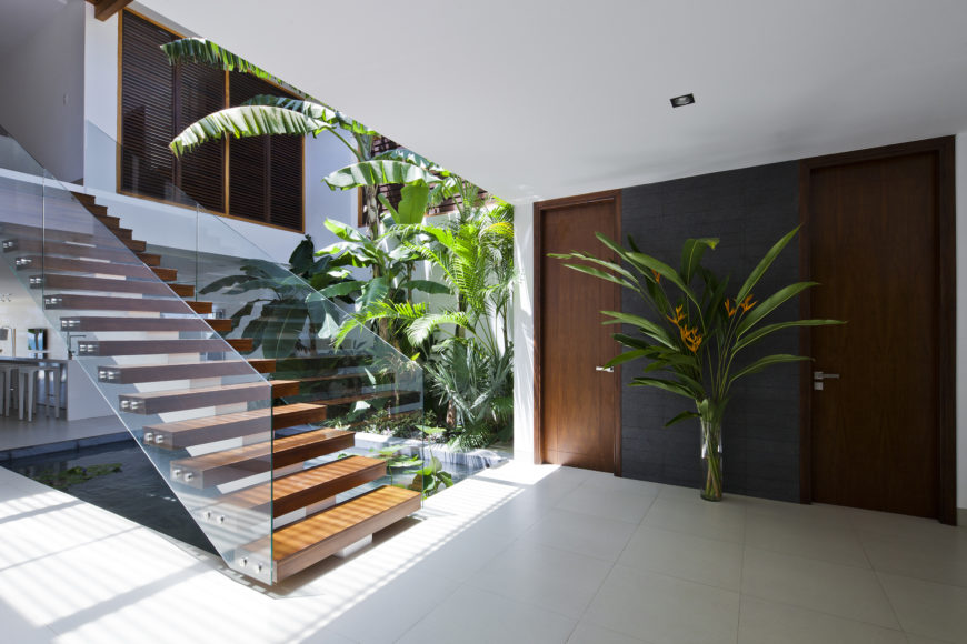 The cozy main entryway features more dark natural wood, white tile, and greenery throughout. Guests coming in see this beautiful pond immediately.