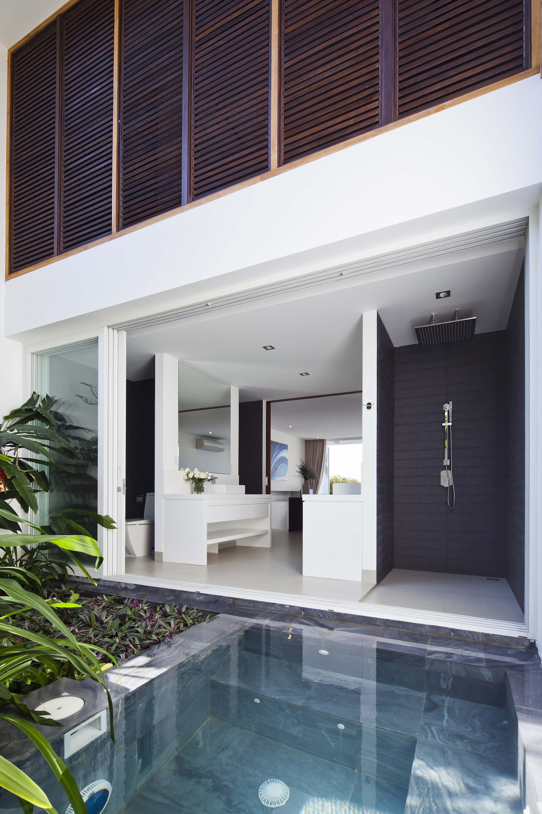 Next to the pool we see one of the bathrooms fully opened. White vanities match bedroom decor, while dark paneled shower stands at right. Timber louvers hang above.