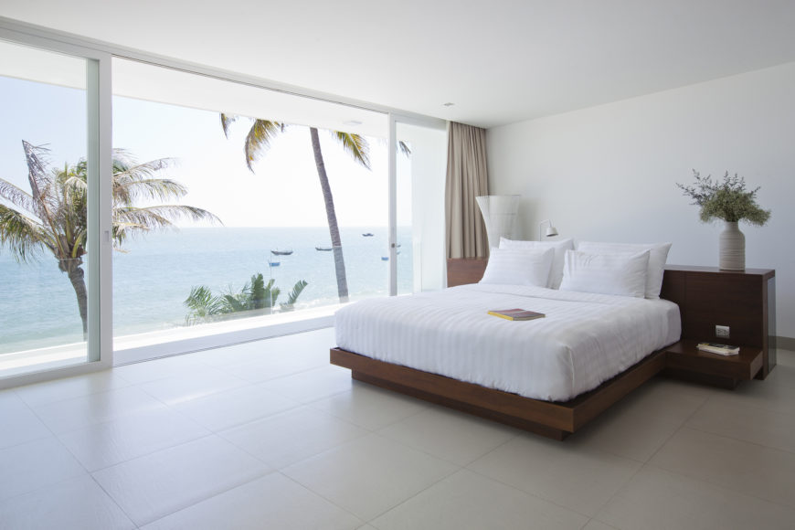 Master bedroom featuring another combination desk and bed frame in rich dark wood, overlooking the ocean via floor to ceiling sliding glass.