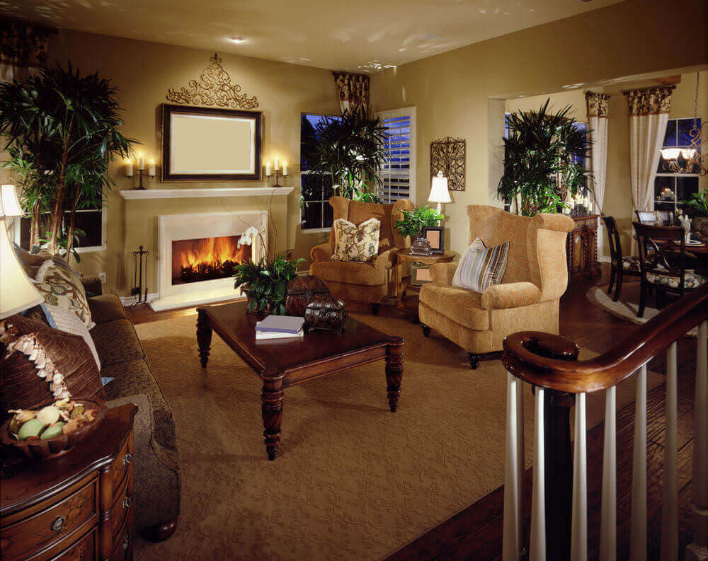 This living room features twin golden rolled arm chairs facing brown floral sofa over a lush