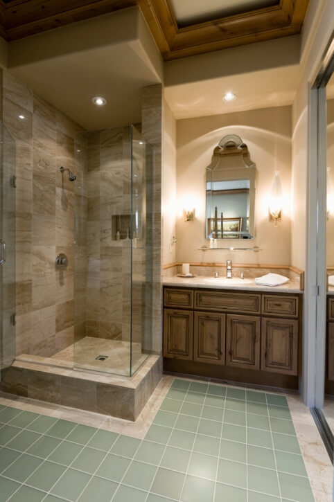 Teal floor tiles contrast with beige marble and dark toned wood vanity in this cozy bathroom, featuring large glass door shower and wood ceiling trim.